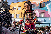 The puppet known as Little Amal continues her 8,000km journey from Turkey, across Europe, through Deptford market in South London and on to other UK cities, on 22nd October 2021, in London, England. Little Amal is a 3.5 metre high character who represents migration - a refugee girl fleeing conflict.