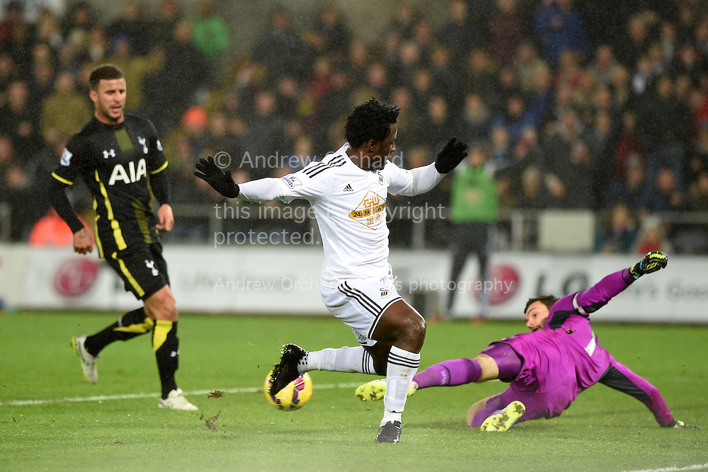 Swansea city's Wilfried Bony is denied by Tottenham goalkeeper Hugo Lloris. .Barclays Premier League match, Swansea city v Tottenham Hotspur at the Liberty Stadium in Swansea, South Wales on Sunday 14th December 2014<br /> pic by Andrew Orchard, Andrew Orchard sports photography.