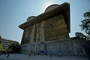 """One of Vienna's Flak (Anti-Aircraft-Gun) Towers 6 of which have been built by the Nazis in World War 2 against Allied bombing raids. Here the """"Geschuetzturm"""" (gun tower) at Arenbergpark. Kids playing soccer at an adjacent playground."""