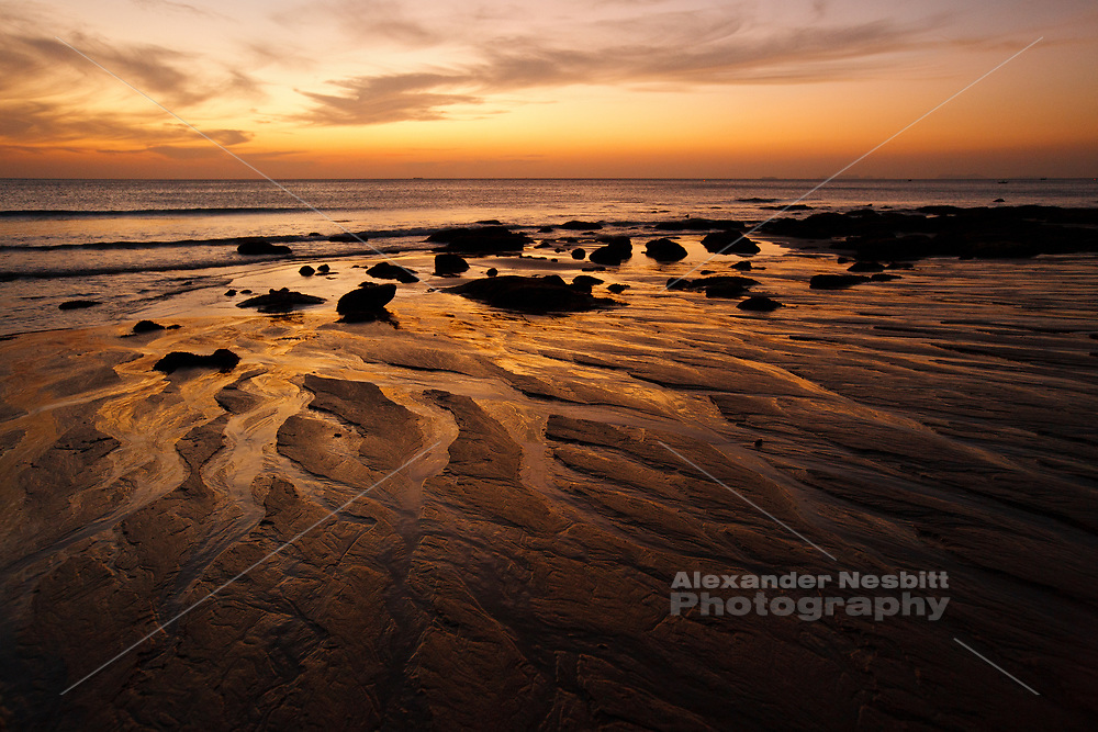 Sunsets directly offshore over the Andaman sea, Koh Lanta, Thailand. An outgoing tide leaves a fascinating pattern of miniature river ways like a giant epic landscape.