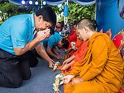 11 AUGUST 2015 - BANGKOK, THAILAND: An man makes an offering to Buddhist monks during a service to honor Queen Sirikit of Thailand before her 83rd birthday. Queen Sirikit was born Mom Rajawongse Sirikit Kitiyakara on August 12, 1932. She is the queen consort of Bhumibol Adulyadej, King (Rama IX) of Thailand. She met Bhumibol in Paris, where her father was the Thai ambassador. They married in 1950, she was appointed Queen Regent in 1956. The King and Queen had one son and three daughters. She has not made any public appearances since her hospitalization in 2012. Her birthday is celebrated as Mother's Day in Thailand, schools and temples across Thailand hold ceremonies to honor the Queen and mothers.       PHOTO BY JACK KURTZ