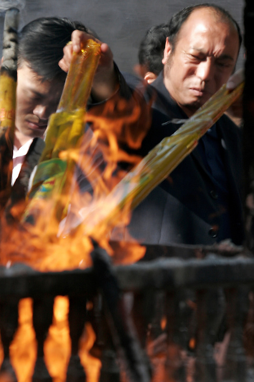 Daoists gather at the large front burner and light incense at Baiyuguan.  Baiyuguan,called White Cloud Temple in English, is over 1,200 years old and stands the south west of Beijing, China.  White Cloud Temple is the largest Daoist structure in Beijing and home of the Dragon Gate sect of Daoism.