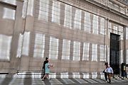 In the week that many more Londoners returned to their office workplaces after the Covid pandemic, City workers walk past sun reflections on the walls of the Bank of England in the City of London, the capital's financial district, on 8th September 2021, in London, England.