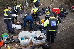 © Licensed to London News Pictures . 21/03/2014 . Barton Moss , Manchester , UK . Police work to cut the men free . Two men lock themselves together using concrete and metal pipes and lie in the middle of the road down which lorries from the iGas site need to pass . The Barton Moss anti-fracking demonstration camp today (Friday 21st March 2014) . Photo credit : Joel Goodman/LNP