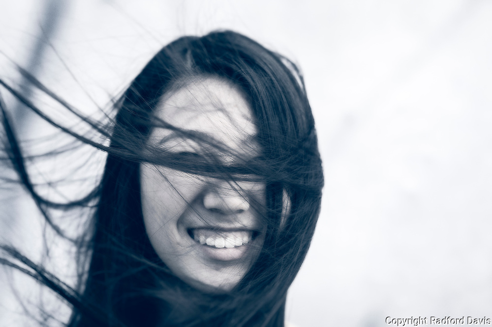 Girl in a cool wind with flying hair.