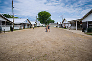 21 JULY 2020 - COLFAX, IOWA: People walk between the barns at the Jasper County Fair in Colfax, about 30 miles east of Des Moines. Summer is county fair season in Iowa. Most of Iowa's 99 counties host their county fairs before the Iowa State Fair. In 2020, because of the COVID-19 (Coronavirus) pandemic, many county fairs were cancelled, or scaled back to concentrate on 4H livestock judging. The Iowa State Fair was cancelled completely. The Jasper County Fair cancelled most events and focused on just the 4H contests. Tuesday were the swine contests.               PHOTO BY JACK KURTZ
