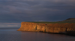 © Licensed to London News Pictures. <br /> 23/03/2015. <br /> <br /> Saltburn, United Kingdom<br /> <br /> The last rays of evening sunlight light up the cliff face of Huntcliff in Saltburn in Cleveland.<br /> <br /> Photo credit : Ian Forsyth/LNP