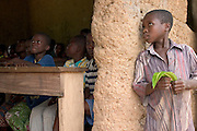 Young togolese boy peeking into a classroom in a small village along the Togolese border, Eastern Ghana. Thousands of Togolese citizens crossed the border into Ghana after the violence that followed presidential elections in April 2005. Partly because of strong cultural ties between populations on both sides of the border, Togolese refugees were able to enjoy the relative hospitality of their Ghanaian neighbours, and are today scattered in various villages across the border. The UNHCR complains that, since the refugees aren't concentratred in large camps, media attention has been minimal, and that it has been very difficult to attract funding.