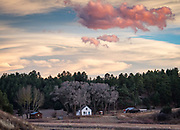 A fall sunset glows over a ranch home on CO 69 north of Westcliffe.  Presented at Art for the Sangres, as a framed photographic canvas: $475.