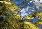 Sunlight reflects in ripples from the outlet of Upper Bagley Lake, on the Chain Lakes Loop Trail, in Mount Baker Snoqualmie National Forest, Washington, USA