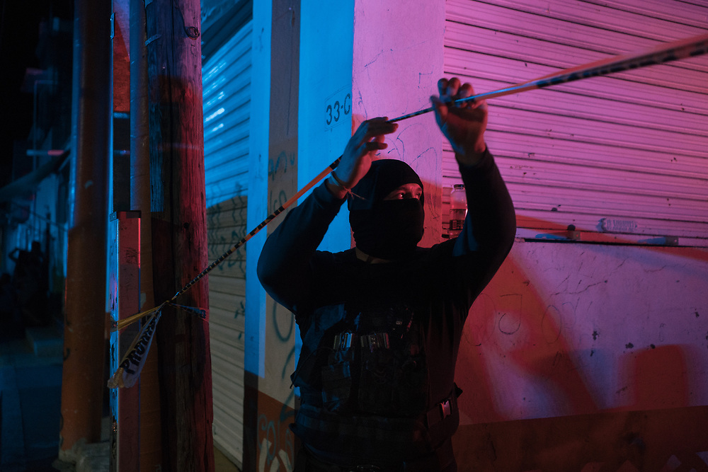 A municipal police officer in Mexico's Zacatecas city holds up caution tape at the scene of a shooting. During decades of authoritarian government, senior federal officials quietly refereed between cartels. State and local authorities fell in line, accepting bribes to look the other way as heroin or marijuana flowed through their states. Mexico's democratization has changed the equation. Now, local governments are more autonomous. Crime groups increasingly are seeking influence at the municipal and state level, through threats or bribery. The country's precarious justice system has proved incapable of checking such graft.