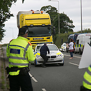 Anti-fracking  activists and protesters outside the gates of Quadrilla's fracking site June 31st, Lancashire, United Kingdom. As a truck with equipment arrives police move in to clear the road. The struggle against fracking in Lancashire has been going on for years. The fracking company Quadrilla is finally ready to bring in a drill tower to start drilling and anti-frackinhg activists are waiting in front of the gates to block the equipment getting in.