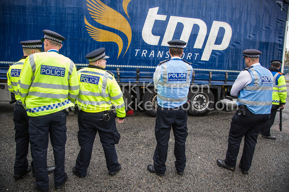 London, UK. 6 September, 2019. Metropolitan Police officers monitor an activist locked beneath a truck making a delivery to ExCel London for DSEI, the world's largest arms fair. The road remained blocked for several hours. The fifth day of protests against the arms fair was themed as Stop The Arms Fair: Stop Climate Change in order to highlight links between the fossil fuel and arms industries.