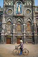 Vietnamese woman wearing a conical hat and blue boots rides her bicycle past an old church along Road 21, Hai Hau District, Nam Dinh Province, Vietnam, Southeast Asia