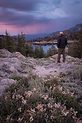 A man watches a distant mountain storm approaching Lower Kinney Lake, Toiyabe National Forest, California