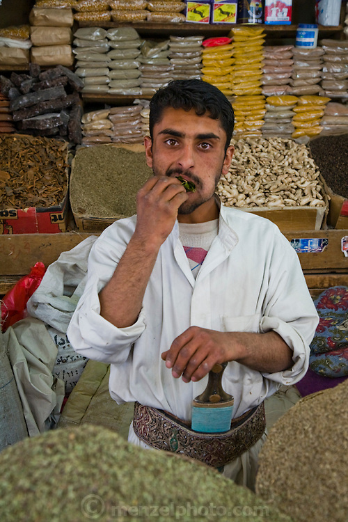 A dry goods seller chews qat while wearing a traditional dagger at his market stall in Sanaa, Yemen.