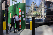 Two businessmen pass close to each other, next to a construction hoarding for a future office building.