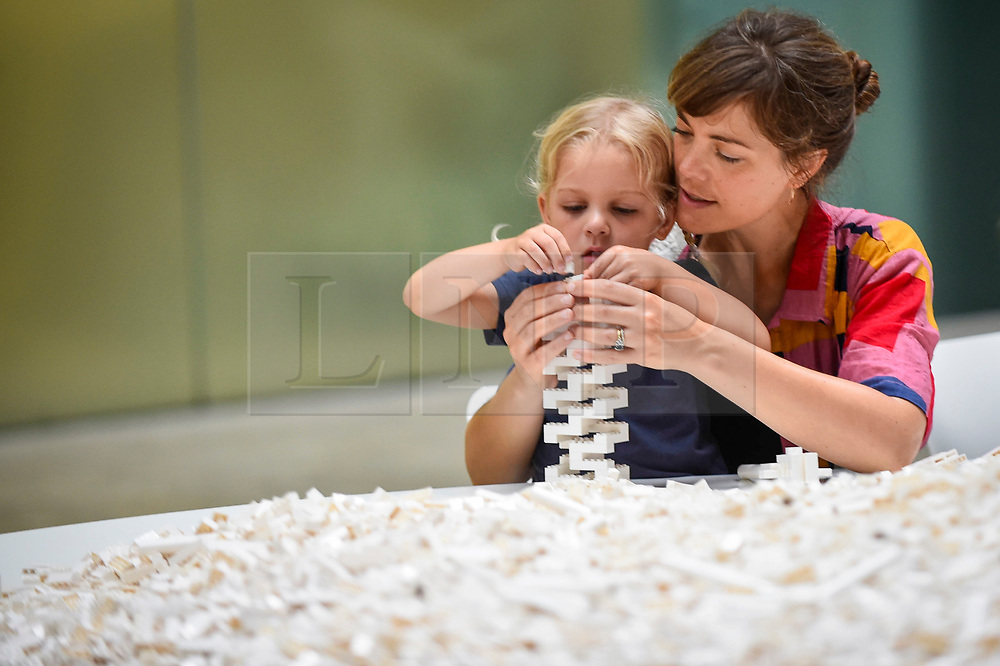 """© Licensed to London News Pictures. 26/07/2019. LONDON, UK. Margot Cartwright-Naylor, aged 4, and her mother work with Lego at the preview of """"The cubic structural evolution project"""", 2004, by Olafur Eliasson at Tate Modern.  Exhibited for the first time in the UK, the artwork comprises one tonne of white Lego bricks inspiring visitors to create their own architectural vision for a future city and is on display until 18 August 2019.  The work coincides with the artist's new retrospective exhibition """"In real life"""" at Tate Modern on display to 5 January 2020.  Photo credit: Stephen Chung/LNP"""
