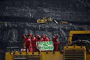 Hundreds of environmental activists stopping the open cast coal mine Ffos-y-Fran near Merthyr Tydfil, Wales from operating May 3rd 2016. Unchallenged by security the activists enter the mine which is not in operation and empty for any other activity and set up banners and form a symbolic red line in the black sand. The activists from Reclaim the Power wants the mine shut down and a moratorium on all future open coal mining in Wales. The group Reclaim the Power had set up camp near by and had over three days prepared the action and up to 300 activists all dressed in red went into the mine in the early morning. The activist were plit in three groups and carried various props signifying the red line in the sand, initially drawn in Paris at the COP21. The mine is one of the largest open cast coal mines in the UK and is run by Miller Argent who have to date extracted 5million tons of coal. The activists entered the mine unchallenged by any security or police and the protest went on peacefully till mid afternoon with no arrests made.  Open coal mining is hugely damaging to the local environment and  contributing to global climate change.