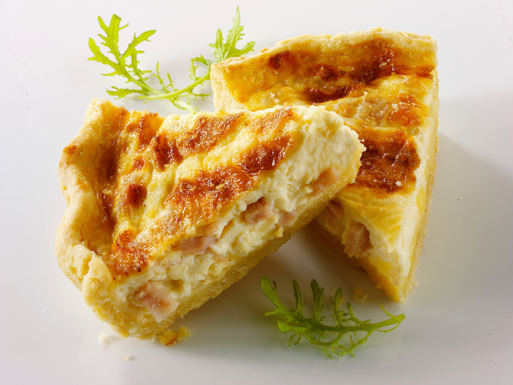 Slices of quiche Loraine on a white background