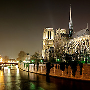 Notre Dame de Paris at night. This is the view of the back, with the Seine in the foreground.
