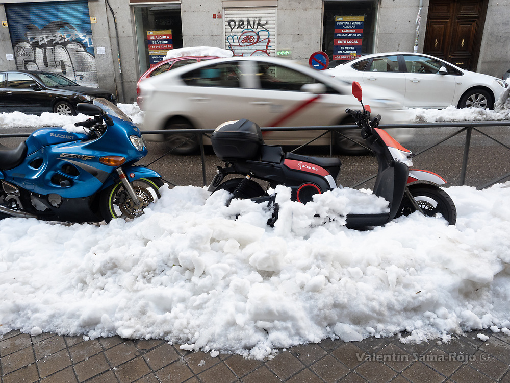 Madrid, Spain. 14th January, 2021. Two bikes stacked in a pile of frozen snow at Madrid's downtown. Madrid's municipal cleaning services are working partially after storm Filomena, works are focused on clearing the streets but trash removal services are not fully operative. © Valentin Sama-Rojo.