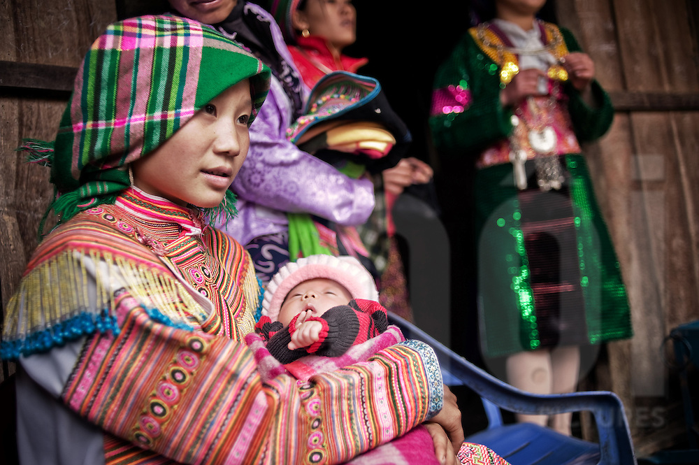 A young Hmong woman dressed in colorful traditional clothes holds her baby in her arms, Ha Giang Province, Vietnam, Southeast Asia