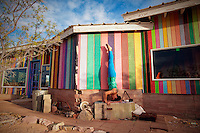 Woman holding a headstand next to a colorful house.