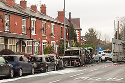 © Licensed to London News Pictures . 08/02/2013 . Salford , UK . Pictured a van and a row of cars understood to have been parked when the collision took place whilst behind under a green tarpaulin , the remains of a red Audi on its side . The scene on Leigh Road where a multi-vehicle pile up killed two , sparked a fire and damaged several cars and houses overnight , causing residents to be evacuated . Greater Manchester Police report seeing a stolen red Audi which they attempted to pursue prior to the crash . Photo credit : Joel Goodman/LNP