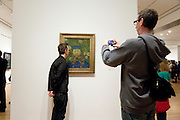 tourist making a funny picture of them self with a Van Gogh painting Museum of Modern Art NY