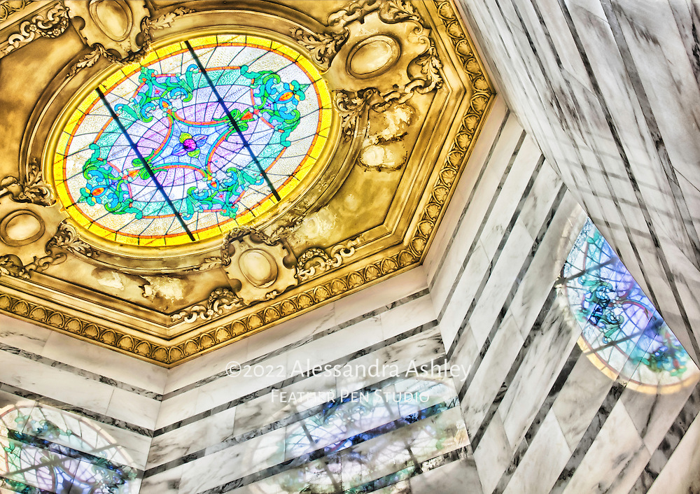 Stained glass, gold-framed skylight creates reflections in stairwell of historic building.