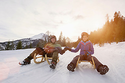 Couple sledding on winter landscape