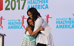 Former first lady Michelle Obama hugs Bruktawit Tesfaye before speaking at the Healthier America's 2017 summit on May 12, 2017 at the Renaissance hotel in Washington, DC. Photo by Olivier Douliery/ Abaca