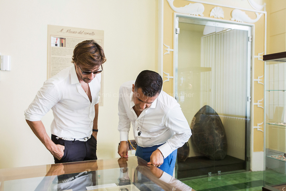 """TORRE DEL GRECO, ITALY - 13 JULY 2016: Amedeo Scognamiglio, master-carver and founder of Amedeo, a collection of modern-day Cameos and avant-garde artisan jewels, and his business partner and long-time childhood friend Roberto Faraone Mennellal look at historical cameos displayed here in the Museo del Corallo (Coral Museum), hosted since 2009 by the """"Francesco Degni"""" Artistic High School, founded in 1878 and historically known as the """"Scuola del Corallo"""" (Coral School), in Torre del Greco, Italy, on July 13th 2016.<br /> <br /> Amedeo Scognamiglio learned the art of carving of cameos at the age of 16 years old in his father's company (M+M Scognamiglio), continuing an artistic manufacturing tradition of a six generations family of coral and cameo manufacturers dating back to the early 1800s in Torre del Greco, a town at the foot of Mount Vesuvius, Italy. Amedeo's design philosophy aims at a contemporary approach to the ancient art of cameo making, through alternative materials, unexpected ideas and smile-triggering designs. In 2001, Amedeo Scognamiglio partnered with his long-time childhood friend Roberto Faraone Mennella to create a fine jewelry line called Faraone Mennella by R.F.M.A.S. Group.The designer duo created a line that brings together the quality and craftsmanship of fine Italian jewelry to the world of fashion accessories. In 2006, the opening of AMEDEO, a Boutique on the chic Upper East Side in NYC, dedicated to the Designer's vision of Cameos, and followed shortly after by another opening in Capri, Italy."""