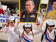 """14 JULY 2013 - BANGKOK, THAILAND:  Royalist supporters of the Thai monarchy hold up signs of Bhumibol Adulyadej, the King of Thailand, and his wife Queen Sirikit during an anti-government protest in Bangkok Sunday. About 150 members of the so called """"White Mask"""" movement marched through the central shopping district of Bangkok Sunday to call for the resignation of Yingluck Shinawatra, the Prime Minister of Thailand. The White Mask protesters are strong supporters of the Thai monarchy. They claim that Yingluck is acting as a puppet for her brother, former Prime Minister Thaksin Shinawatra, who was deposed by a military coup in 2006 and now lives in exile in Dubai.       PHOTO BY JACK KURTZ"""