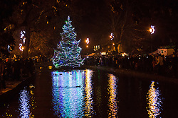 © Licensed to London News Pictures 02/12/2016, Bourton on the Water, UK. The annual turning on of the Christmas tree lights in Bourton on the Water in the Cotswolds. The tree is always placed in the centre of the small river running through the village.Photo Credit : Stephen Shepherd/LNP