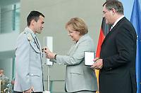 06 JUL 2009, BERLIN/GERMANY:<br /> Oberfeldwebel Markus Geist  (L), Angela Merkel (M), und Franz Josef Jung (R), CDU, Bundesverteidigungsminister, waehrend der Ueberreichung der ersten Ehrenkreuze der Bundeswehr fuer Tapferkeit, Bundeskanzleramt<br /> IMAGE: 20090706-01-042