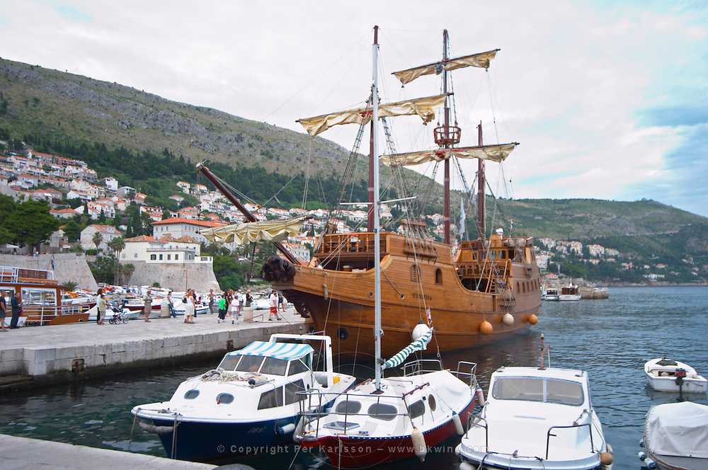 The Karaka 16 century galleon replica boat in the old harbour. Other boats moored. Dubrovnik, old city. Dalmatian Coast, Croatia, Europe.
