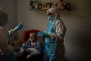 SANT ANDREU DE LA BARCA, SPAIN - MAY 13: Primary health care nurses Monica Gimenez (L) and Mari Paz both in personal protective equipment (PPE) perform a swap test for COVID-19 to Josefa Langa after presenting symptoms during a monitoring visit to COVID19 patients at Can Sunyer nursing home on May 13, 2020 in Sant Andreu de la Barca, Spain. As figures of deaths and infection rates are at their lowest since the start of the outbreak in Spain, the primary health care network will be crucial for filtering and monitoring COVID-19 patients, in order to protect Spanish hospitals from becoming over-crowded. This task will be especially intense across Spain's nursing homes, where more than 18,000 elderly people have died due to the Coronavirus (COVID-19) pandemic.
