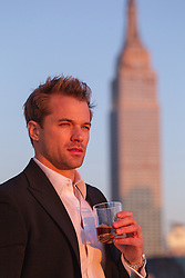 man having a drink outdoors near the Empire State Building in New York City