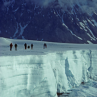 A fly-in ski expedition travels by the edge of a floating ice shelf by Jones Sound on the Antarctic Peninsula, Antarctica.