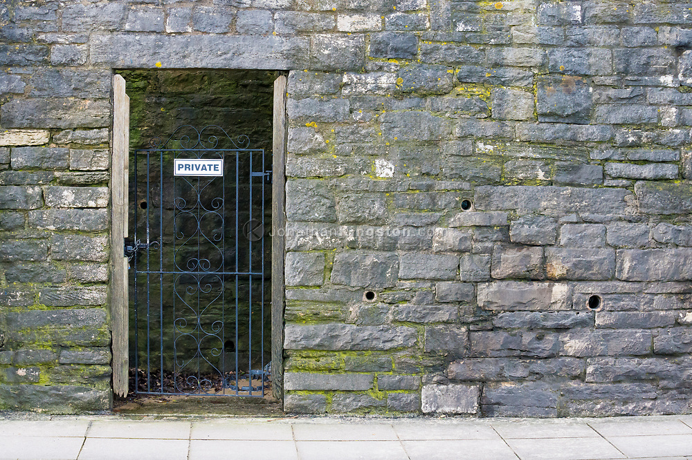 """Locked iron gate with a sign reading """"private"""" on its bars in a stone wall in England."""