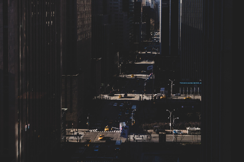 Morning sunlight shining through the streets of NYC with the avenues in contrast.