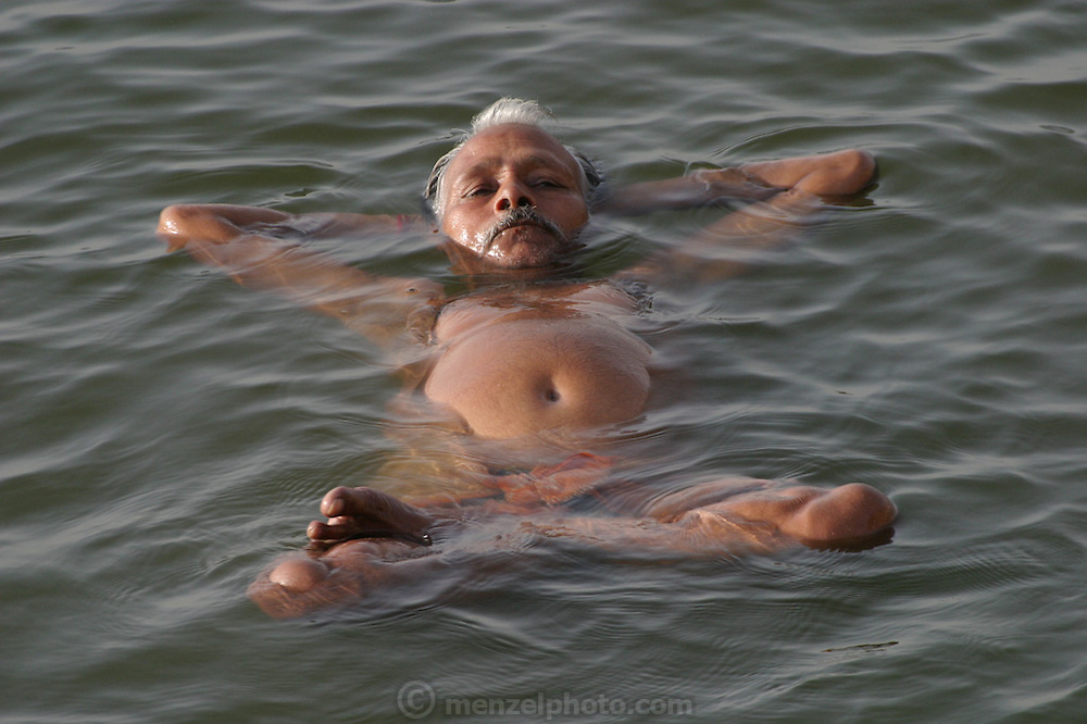 A potbellied man floats during an early morning swim in the river Ganga. Near the Dashashwamedh ghat. Colorful and popular Dasasvamedha Ghat gets a lot of attention from religious pilgrims, locals, and tourists alike and is one of the busiest bathing ghats in the city of Varanasi.