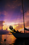 Young couple on bow of anchored sailboat, sunset, US Virgin Islands