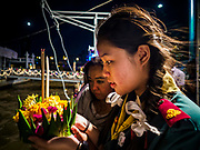 "03 NOVEMBER 2017 - BANGKOK, THAILAND: A Girl Scout prays before floating her krathong during Loi Krathong at Wat Prayurawongsawat on the Thonburi side of the Chao Phraya River. Loi Krathong is translated as ""to float (Loi) a basket (Krathong)"", and comes from the tradition of making krathong or buoyant, decorated baskets, which are then floated on a river to make merit. On the night of the full moon of the 12th lunar month (usually November), Thais launch their krathong on a river, canal or a pond, making a wish as they do so. Loi Krathong is also celebrated in other Theravada Buddhist countries like Myanmar, where it is called the Tazaungdaing Festival, and Cambodia, where it is called Bon Om Tuk.     PHOTO BY JACK KURTZ"