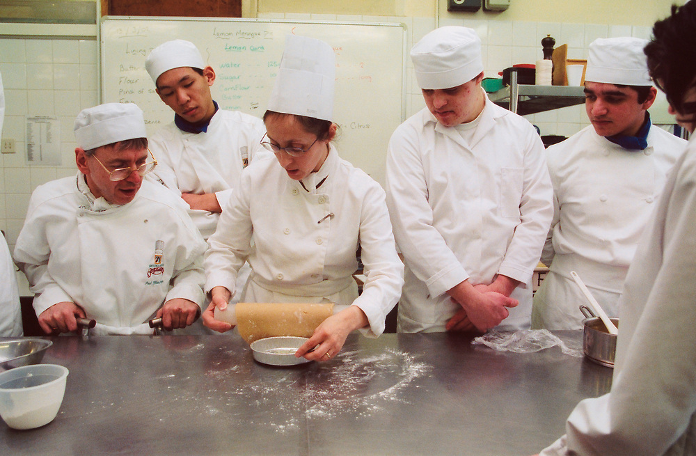 Group of students with learning difficulties on cookery course watch tutor make pastry UK