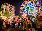 29 OCTOBER 2015 - YANGON, MYANMAR: A human powered Ferris Wheel at a street carnival in central Yangon. Electricity is scarce in Myanmar, especially in rural areas, and most traveling carnivals use human powered rides. Workers climb to the top of the Ferris Wheel and then pull it around getting it spinning. They do the same with Merry Go Rounds, but instead of climbing to the top they pull it around. The carnival coincided with the Thadingyut Festival, the Lighting Festival of Myanmar, which is held on the full moon day of the Burmese Lunar month of Thadingyut, October or November on the Gregorian calendar. The carnival featured food, rides and games.      PHOTO BY JACK KURTZ
