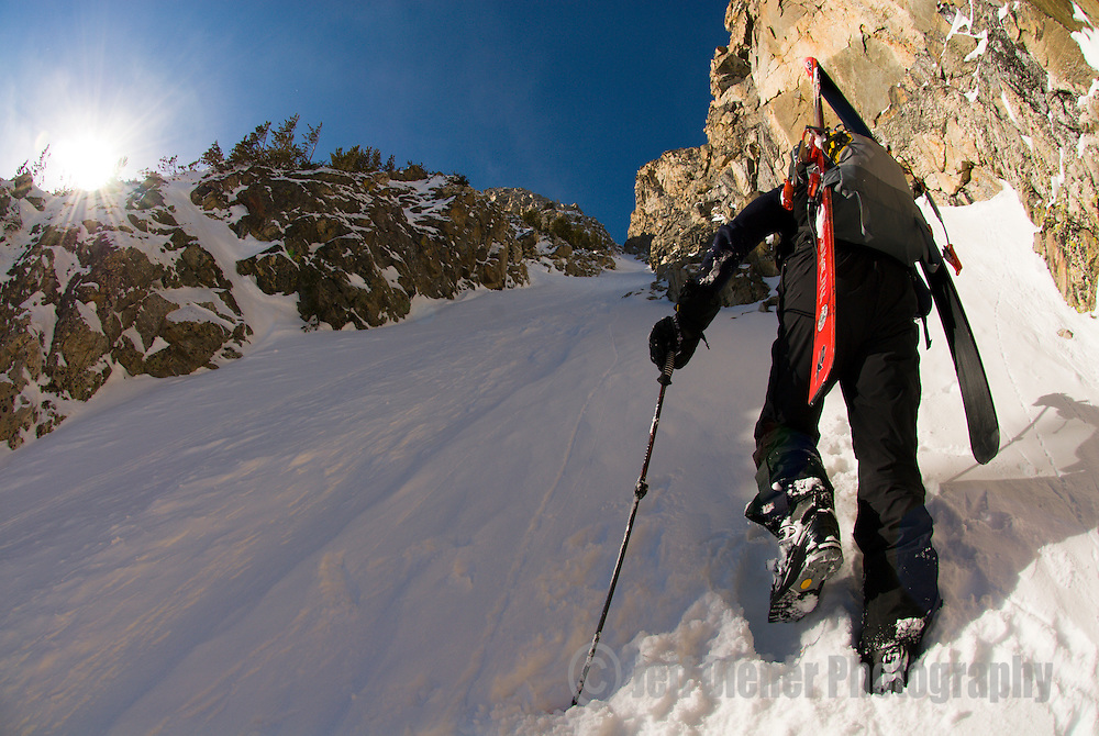 A young man hikes up the Sliver Couloir in Grand Teton National Park,  Jackson Hole, Wyoming.