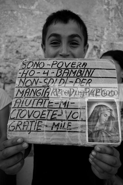 """Un ragazzino """"rom"""" fuori dalla Chiesa dell'Arcangelo Michele che chiede l'elemosina. Questa foto è stata scattata a Mesagne in provincia di Brindisi, durante la celebrazione della festa della Madonna del Carmine il 15 luglio 2010."""